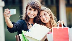 Dos mujeres jovenes que hacen compras en la alameda que toma a Fotografía de archivo libre de regalías