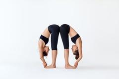 Dos mujeres jovenes que hacen el asana de la yoga que coloca la curva delantera presentan Foto de archivo libre de regalías