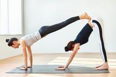 Dos mujeres jovenes que hacen el perro hacia abajo del doble del asana de la yoga Fotografía de archivo libre de regalías
