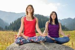 Dos mujeres jovenes que hacen yoga en una roca Foto de archivo
