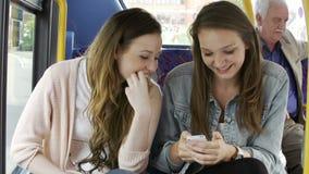 Dos mujeres jovenes que leen el mensaje de texto en el autobús metrajes
