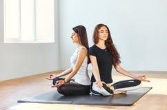 Dos mujeres jovenes que meditan en Lotus Pose Imagenes de archivo