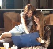 Dos mujeres jovenes que miran el menú Imagenes de archivo