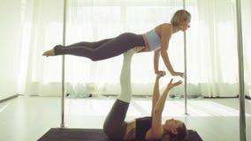 Dos mujeres jovenes que practican yoga acrobática almacen de video