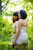 Dos mujeres jovenes que presentan en un parque del verano Fotografía de archivo libre de regalías