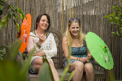 Dos mujeres jovenes que ríen en un banco imagen de archivo