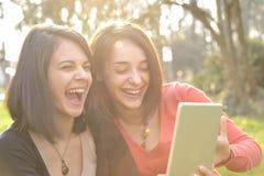 Dos mujeres jovenes que ríen y que se divierten en una tableta Foto de archivo