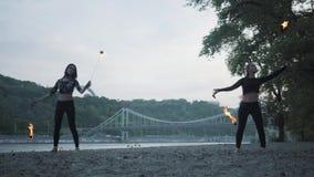 Dos mujeres jovenes que realizan una demostración con las bolas de la llama que se colocan en el riverbank El mostrar femenino de almacen de metraje de vídeo