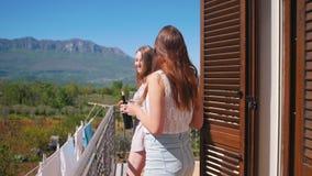 Dos mujeres jovenes que salen en el balcón que sostiene los vidrios y la botella de vino metrajes