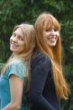 Dos mujeres jovenes que se colocan de nuevo a la parte posterior Fotos de archivo libres de regalías