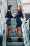 Dos mujeres jovenes que se colocan en los pasos de la escalera m?vil en el centro de negocios fotos de archivo