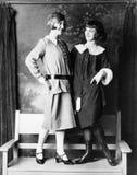 Dos mujeres jovenes que se colocan en un banco que sonríe y que mira uno a (todas las personas representadas no son vivas más lar Fotos de archivo