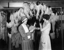 Dos mujeres jovenes que se colocan en una tienda y una sonrisa de ropa (todas las personas representadas no son vivas más largo y Foto de archivo