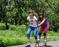 Dos mujeres jovenes que se divierten rollerblading Fotografía de archivo