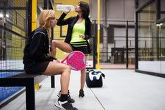 Dos mujeres jovenes que se relajan después del tenis de la paleta hacen juego Imagenes de archivo