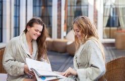 Dos mujeres jovenes que se relajan en el balneario que lee la revista Fotografía de archivo libre de regalías