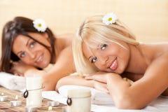 Dos mujeres jovenes que se relajan en el centro del balneario Imagen de archivo