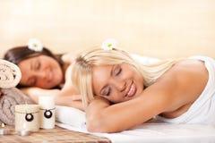 Dos mujeres jovenes que se relajan en el centro del balneario Foto de archivo libre de regalías
