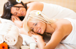 Dos mujeres jovenes que se relajan en el centro del balneario Foto de archivo