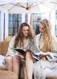 Dos mujeres jovenes que se relajan en el traje toweling que lleva del balneario Fotografía de archivo