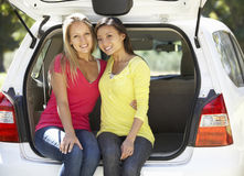 Dos mujeres jovenes que se sientan en el tronco del coche Fotos de archivo