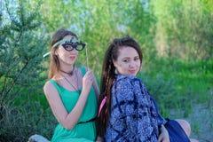 Dos mujeres jovenes que se sientan en la hierba que tiene buen tiempo Imagen de archivo libre de regalías