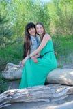 Dos mujeres jovenes que se sientan en la hierba que tiene buen tiempo Foto de archivo libre de regalías