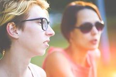 Dos mujeres jovenes que se sientan en un banco en el parque Fotografía de archivo libre de regalías