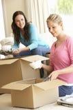 Dos mujeres jovenes que se trasladan al nuevo hogar que desempaqueta las cajas Imagen de archivo libre de regalías