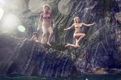 Dos mujeres jovenes que se zambullen de un acantilado en el mar Fotografía de archivo