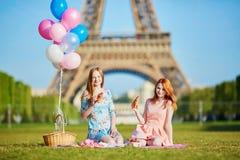 Dos mujeres jovenes que tienen comida campestre cerca de la torre Eiffel en París, Francia imágenes de archivo libres de regalías
