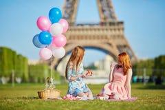 Dos mujeres jovenes que tienen comida campestre cerca de la torre Eiffel en París, Francia imagenes de archivo