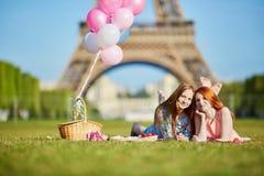 Dos mujeres jovenes que tienen comida campestre cerca de la torre Eiffel en París, Francia fotografía de archivo libre de regalías