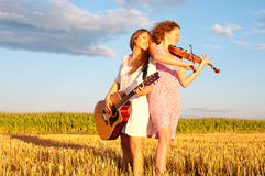 Dos mujeres jovenes que tocan la guitarra Fotografía de archivo libre de regalías