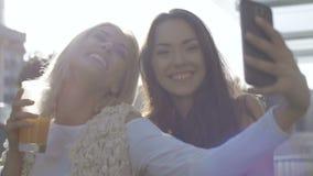 Dos mujeres jovenes que toman el selfie con el teléfono móvil metrajes