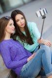 Dos mujeres jovenes que toman imágenes con su smartphone Imagen de archivo libre de regalías