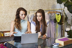 Dos mujeres jovenes que trabajan en tienda de ropa Imagen de archivo