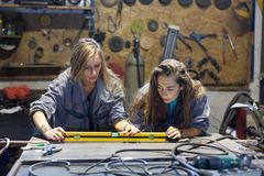 dos mujeres jovenes que trabajan en una tienda del mecánico fotos de archivo libres de regalías