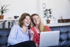 Dos mujeres jovenes que usan el ordenador mientras que se sienta en el sofá en la vida imagen de archivo