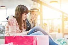 Dos mujeres jovenes que usan la tableta que hace compras en línea Fotos de archivo libres de regalías