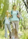 Dos mujeres jovenes que van de excursión entre los árboles Fotos de archivo libres de regalías