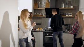 Dos mujeres jovenes rubias están bailando en cocina en un partido en el sitio de la universidad, bebiendo el champán con sus amig metrajes