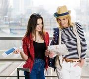 Dos mujeres jovenes se colocan con una maleta en el ferrocarril o el aeropuerto Mire la tarjeta y el pasaporte Foto de archivo libre de regalías