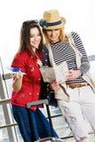 Dos mujeres jovenes se colocan con una maleta en el ferrocarril o el aeropuerto Mire la tarjeta y el pasaporte Fotografía de archivo libre de regalías