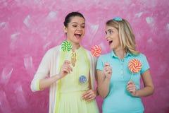 Dos mujeres jovenes se divierten con las piruletas, celebrando conce del partido Imagen de archivo