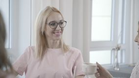 Dos mujeres jovenes se sientan en un café y comunican con sus amigos almacen de video
