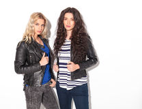 Dos mujeres jovenes serias en las chaquetas de cuero que sostienen sus cuellos Fotos de archivo