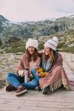 Dos mujeres jovenes sirven un termo y una taza caliente imagenes de archivo