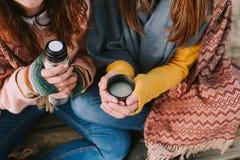 Dos mujeres jovenes sirven un termo y una taza caliente foto de archivo