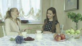 Dos mujeres jovenes sonrientes atractivas elegantes que tienen tiempo del café en la mesa de comedor almacen de metraje de vídeo
